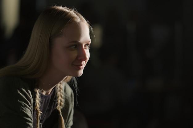 プロファイルの暗い部屋に座っているきれいな女の子の肖像画