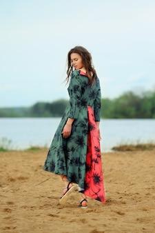 Красивая одинокая девушка, прогулки по песку у озера в пасмурный день