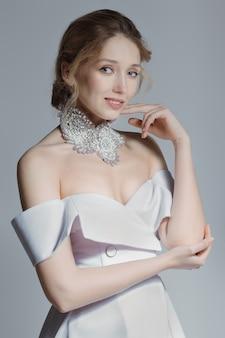 コンセプトのウェディングドレスの美しい花嫁の柔らかい肖像画。ジャケットスタイルの襟と深いデコルテ、羽毛、ストッキング。