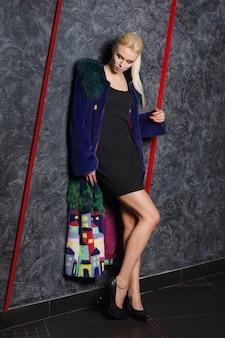 Привлекательная девушка в коротком черном платье, длинная шуба позирует возле холодной морозной стены