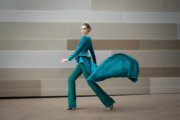 空を飛んでいる彼女のドレスとファッションの女性の完全な長さの肖像画