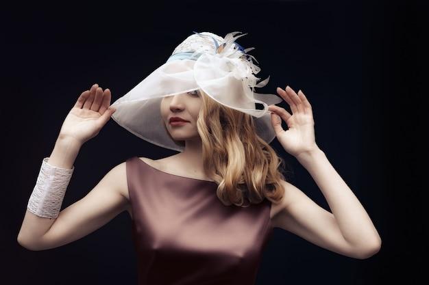 シルクのドレスと広い帽子のポーズで美しい女性