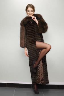 壁に近いポーズの毛皮のコートで長い脚を持つ魅力的な女性の肖像画。ナチュラルメイク。