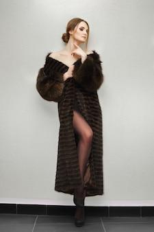 目を閉じて壁に近いポーズの毛皮のコートで長い脚を持つ魅力的な女性の肖像画。