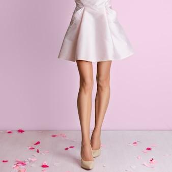 完璧なスリムな長い女性の足とピンクのドレス
