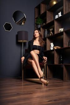 部屋のモダンなアームチェアに座っているミニスカートと特大の黒のジャケットの魅力的な女性