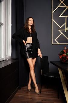Скромная милая девушка в мини-юбке и куртке стоит возле стола