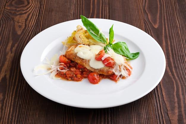 ローストチキンフィレ、トマトチェリー、パルメザンチーズ、クルトン、暗い木製のテーブル