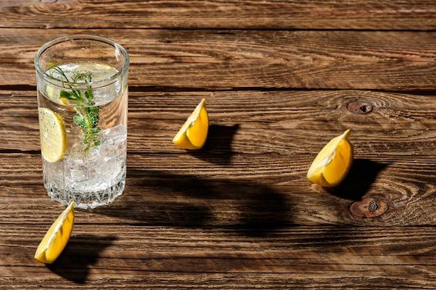 Газированная холодная вода со льдом и лимоном отбрасывает тень на деревянный стол