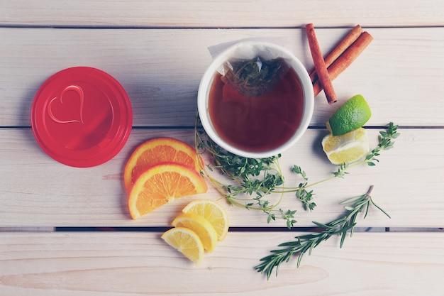 オレンジ、ライム、レモンのテイクアウトカップでハーブティーとテーブルのトップビュー
