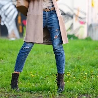 緑の芝生でポーズのボーイフレンドジーンズの女性の足