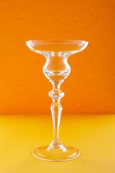 Пустой стакан для коктейля или десерта на оранжевой стене