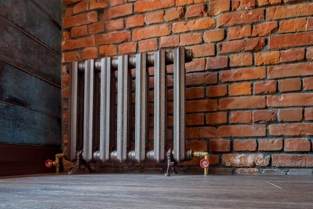 足が付いている家のためのビンテージ鉄のラジエーター。古い鋳鉄製セントラルヒーティングバッテリー。