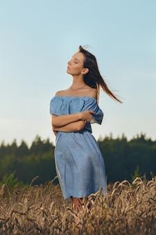 日没時の麦畑の美しい若い女性
