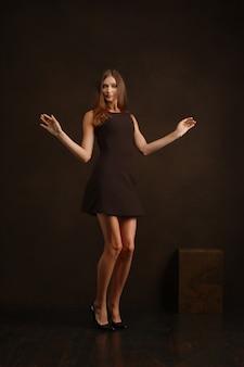 手を振って暗い壁の近くダンスショートドレスで幸せな女