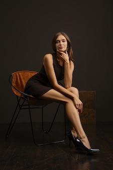 Привлекательная фотомодель с длинными ногами позирует в коротком узком платье