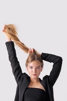 それらを持ち上げて彼女の長いストレートの髪で遊ぶかわいい女性のクローズアップの肖像画