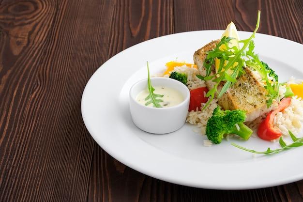 Крупным планом вид жареного судака с рисом, болгарским перцем и рукколой, подается с майонезным соусом