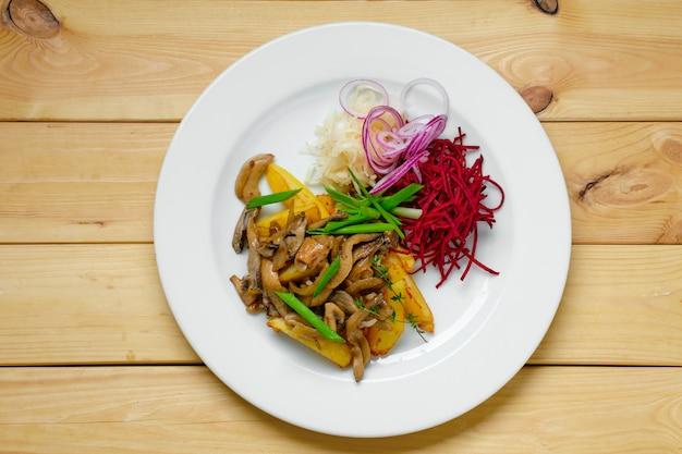 Вид сверху тарелка с жареным картофелем, свеклой, маринованной капустой и грибами