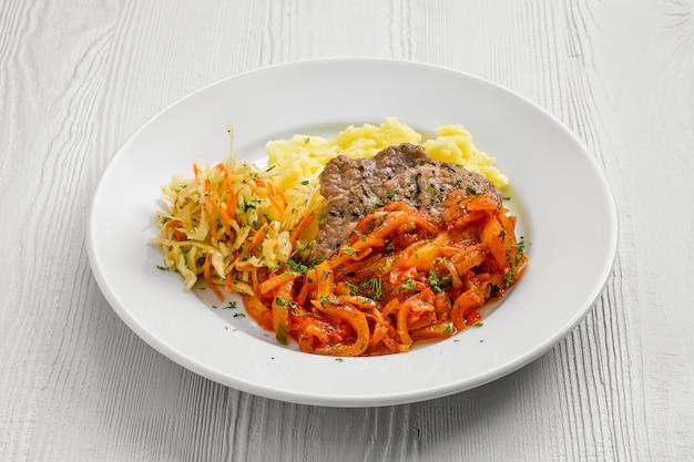 マッシュポテトとキャベツのサラダを添えたピーマンを裏打ちした刻んだ肉のプレート