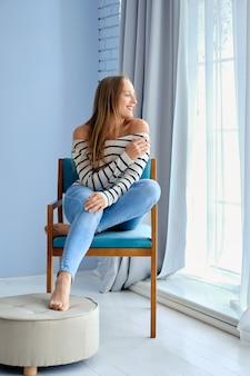 自宅の窓際の居心地の良いアームチェアに座っている女性のライフスタイルの完全な長さの肖像画