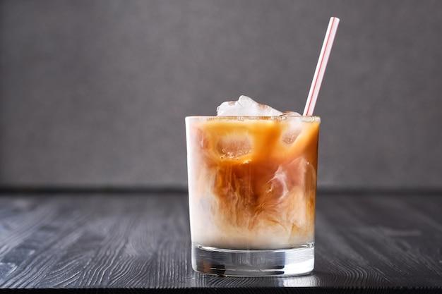 暗い木製のテーブルにクリームとアイスコーヒー