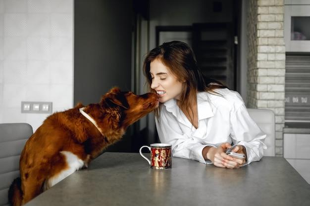 Красивая женщина в белой рубашке сидит с чашкой чая на кухне и играет со своей собакой