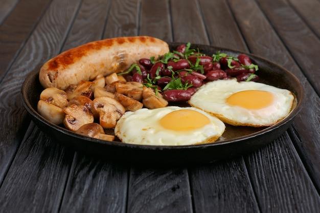 目玉焼き、ソーセージ、マッシュルーム、木製のテーブルの上の豆と鋳鉄のフライパン。ローアングル