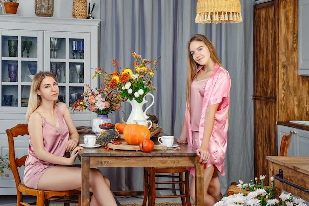 Две молодые девушки пьют чай в деревенской кухне и разговаривают