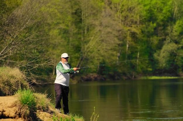 川の土手で回転するルアーを投げる男の魚。週末の屋外アクティビティ。絞り開放で浅い被写界深度の写真。