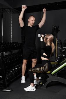 Фитнес-инструктор проводит персональные тренировки для девушки с гантелями перед зеркалом