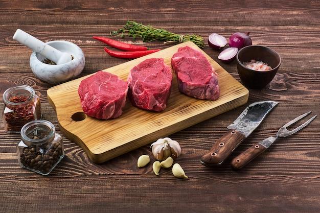 木製のテーブルのスパイスとマリネした生の牛肉ステーキ