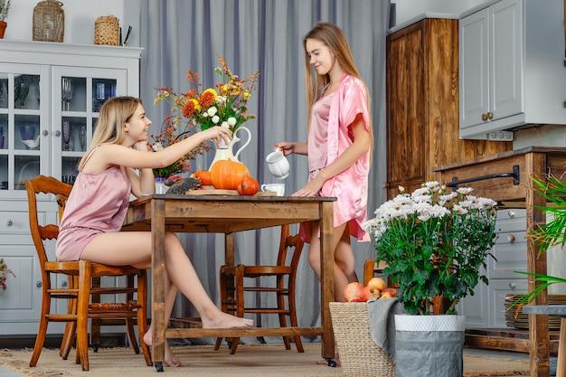 Две сестры сидят друг напротив друга на кухне и разговаривают