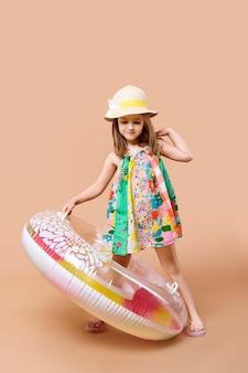 Милый ребенок в сарафане и соломенной шляпе с плаванием играет кольцо