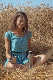 青いサンドレスで美しい少女が麦畑に座っているし、魔法瓶からお茶やコーヒーを飲む