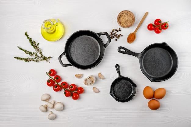 Чугунные сковородки и специи на белой древесине