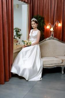 Красивая невеста в лондонском платье сидит на диване у окна