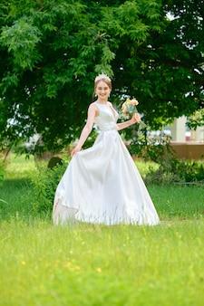 Портрет красивой невесты с короной в волосах на открытом воздухе возле церемонии павильона