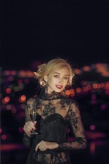 Красивая девушка с бокалом шампанского стоит возле окна