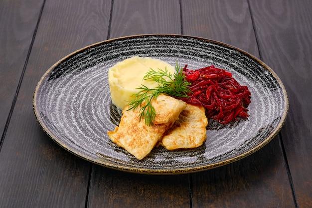 Жареный хек в панировке с картофельным пюре и жареной свеклой на темном деревянном столе