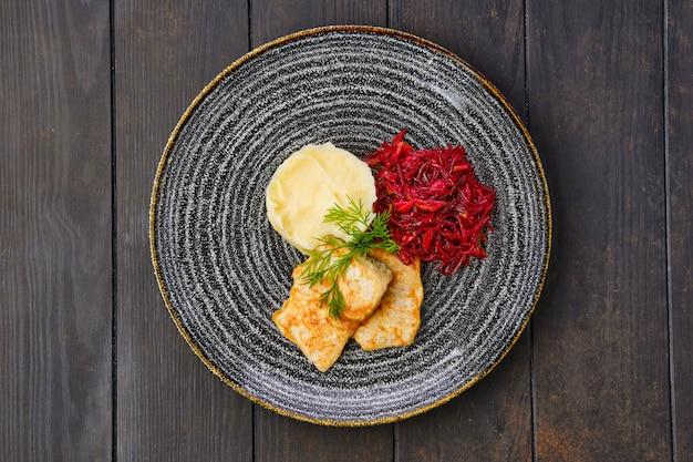 Вид сверху жареного хека в панировке с картофельным пюре и жареной свеклой на темном деревянном столе
