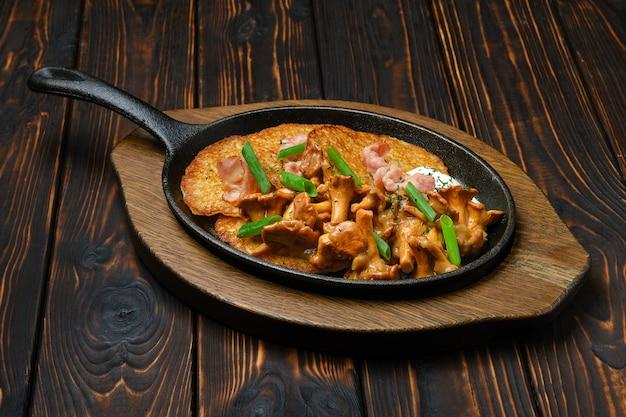 Картофельные оладьи с лисичками и свининой в чугунной сковороде