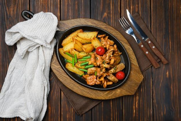 Вид сверху картофельные дольки с лисичками и свинины в чугунной сковороде