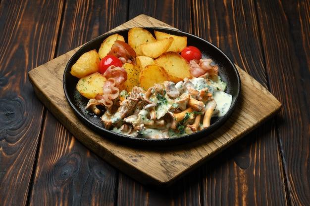 Картофельные дольки с лисичками и свининой в чугунной сковороде