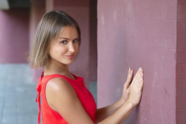 壁に彼女の手で傾いているかわいいトリッキーな若い女性の肖像画