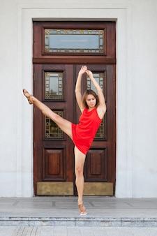 彼女の足を持ち上げるショートドレスでかなり若い女性の完全な長さの肖像画