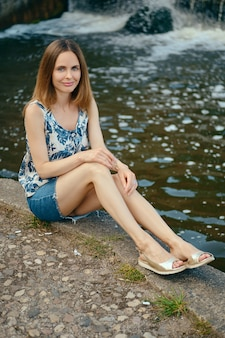 Женщина в блузке без рукавов и джинсовой юбке отдыхает на дачном участке у искусственного водопада