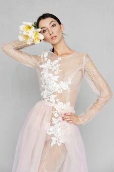 Красотка в бледном прозрачном платье с кружевом позирует с цветами в руках