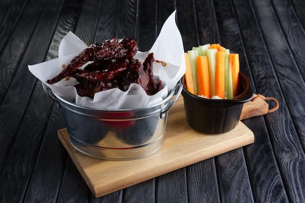 Закуска к пиву. острые куриные крылышки со свежей морковью и сельдереем и соусом