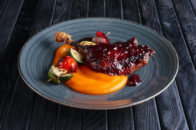 Жареное утиное бедро с морковным пюре и цуккини, перцем и луком на деревянной шпажке
